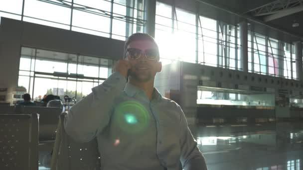 Šťastný mladý podnikatel mluví o telefonu na letišti s odlesk slunce na pozadí. Zavřete portrét pohledný usmívající se obchodník v sluneční brýle mluvit o mobilní telefon v kanceláři. Zpomalený pohyb
