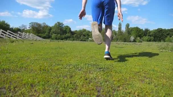 Sportovec se krčí na startovní čáře před závodem a začít běh. Mladý muž na začátku sprint. Pohled zezadu Zpomalený pohyb zpět