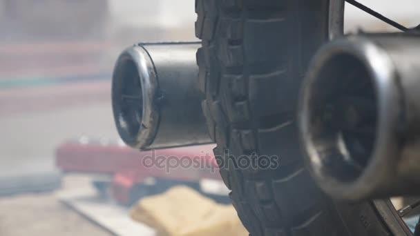 Zblízka staré motocyklové výfukové trubky uvolňující výfukové plyny ve vzduchu. Zpomalený pohyb