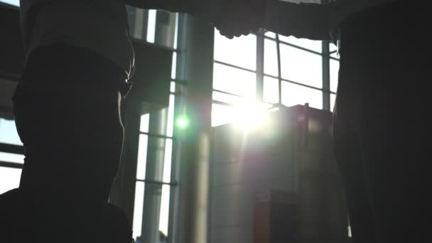 Friendly handshake of two businessmen greeting each other in office. Business handshake indoor. Shaking of male arms. Colleagues meet and shake hands with sun flare at background. Close up Slow motion