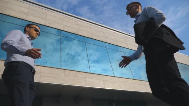 Dva mladí podnikatelé setkání poblíž kanceláře a pozdrav navzájem. Obchodní muž procházející černá Aktovka svého partnera. Kolegové, potřást rukou venkovní v městské pozadí. Detailní záběr Zpomalený pohyb