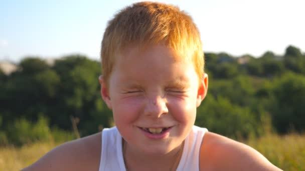 Zblízka emoce mužského potomka s rád výrazem na tváři. Portrét chlapce rád, zrzavé vlasy s pihy se venkovní. Rozkošné hezký dítě s radostným úsměvem při pohledu do kamery. Zpomalený pohyb