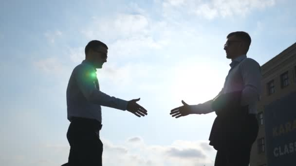 Two young businessmen meeting at city and greeting each other. Colleagues shake hands outdoor. Business handshake outdoor. Shaking of male arms outside. Blue sky with sun at background. Slow motion