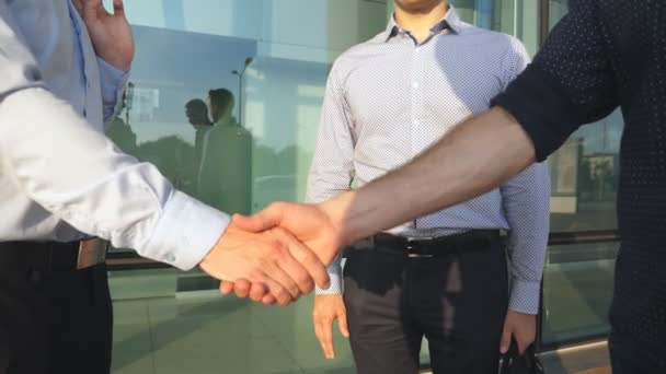 Three businessmen greeting each other in urban environment. Business handshake outdoor. Shaking of male arms outside. Colleagues meet and shake hands in the city background. Close up Slow motion