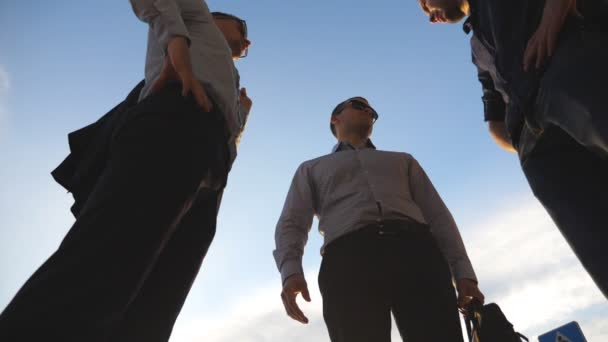 Low angle view of three business men standing outdoor and talking. Businessmen meet and speaking outside in city with blue sky at background. Communication of happy colleagues. Close up Slow motion