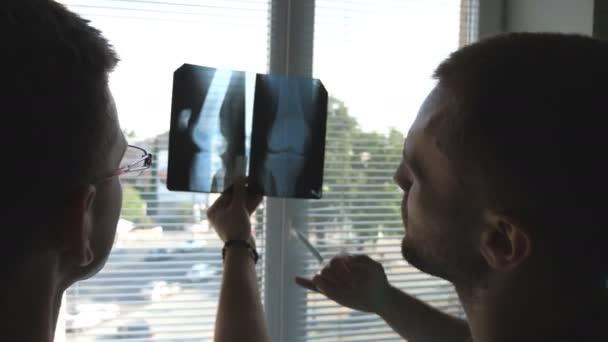 Zdravotníci v nemocnici pohledu a modulárnost rentgenové tisků. Navzájem konzultovat lékaře. Dva lékaři zobrazení mri obrázek a diskutovat o něm. Detailní záběr zadní pohled zezadu