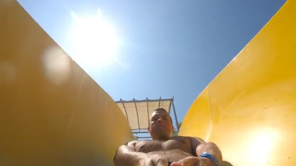 Young happy man sliding down at water slide in aquapark on a beautiful sunny day. Guy with camera in hand having fun and doing self-portrait. Close up Slow motion