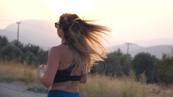 Školení pro Maratonský běh venkovní mladá žena. Sportovní dívka jogging v venkovské silnici. Zdravý aktivní životní styl. Pohled zezadu Zpomalený pohyb zpět