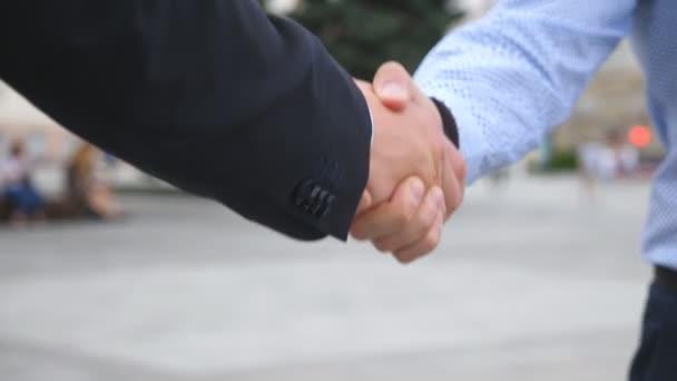 Kolegové setkat a potřást rukou v městské pozadí. Dva podnikatelé navzájem pozdrav v městském prostředí. Obchodní handshake venkovní. Třesení mužské ruce venku. Detailní záběr Zpomalený pohyb