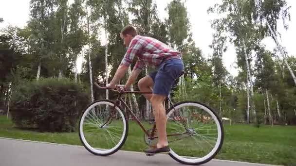 Sledujte pohledný mladík vintage jízdou venkovní. Sportovní chlap, jízda na kole v parku. Zdravý aktivní životní styl. Boční pohled zblízka zpomalené