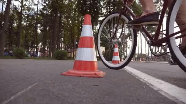 Cyklista jít kolem dopravní kužely. Mladý pohledný muž, jízda historických kol. Sportovní chlap, jízda na kole v parku. Zdravý aktivní životní styl. Nízký úhel pohledu zblízka zpomalené