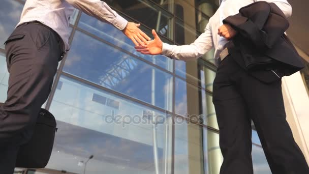 Two businessmen meeting near office building and greeting each other. Business handshake outdoor in urban environment. Shaking of male arms outside. Colleagues shake hands. Close up Slow motion