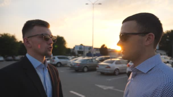 Two young business men standing outdoor near parking and talking. Profile of businessmen in sunglasses speaking outside in the city. Communication of happy colleagues. Close up Slow motion