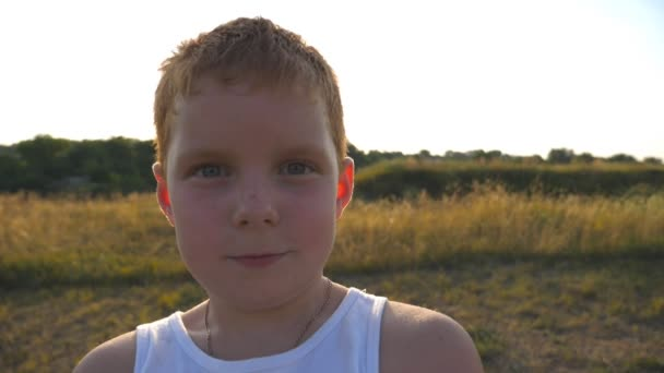 Portrét šťastných dětí s emocí a pocitů na tvář. Malý chlapec je překvapený a usmívá se venkovní. Mladý kluk, zobrazeno radost a usmívá se na hřišti při západu slunce. Detailní záběr Zpomalený pohyb