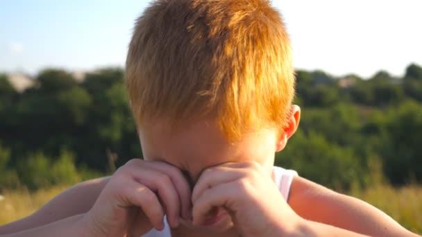 Portrét smutné dětí s emoce a pocity. Mladá zrzavá chlapce s pihy při pohledu na fotoaparát a pláč venkovní. Malé dítě zavřel oči rukama. Detailní záběr Zpomalený pohyb