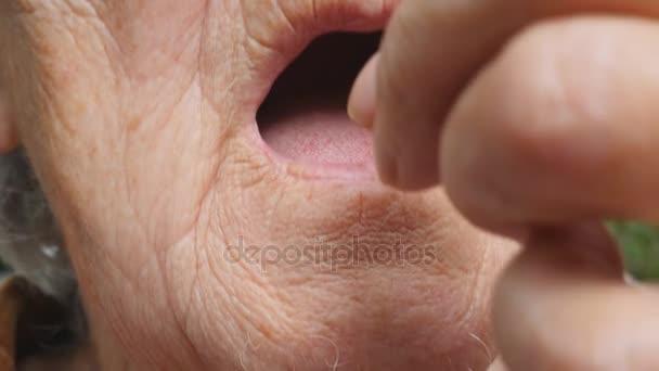 alte Frau, die sich weiße Pillen in den Mund steckt. Großmutter nimmt Tabletten, die ihre gesundheitlichen Probleme lindern. Gesundheitswesen und medizinisches Konzept. Zeitlupe in Nahaufnahme