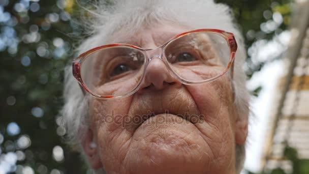 alte Frau richtet ihre Brille auf und blickt nach vorn. Porträt der Großmutter im Freien. Oma mit Brille draußen. niedriger Blickwinkel Nahaufnahme Zeitlupe