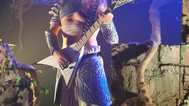 Felismerhetetlen ember játszik a gitár szakaszában rock koncert során. Zenész játszik solo gitár. Elöl lassított nézet bezárása