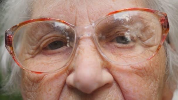 alte Frau mit Brille, die in die Kamera blickt. Nahaufnahme Porträt der Großmutter. Zeitlupe