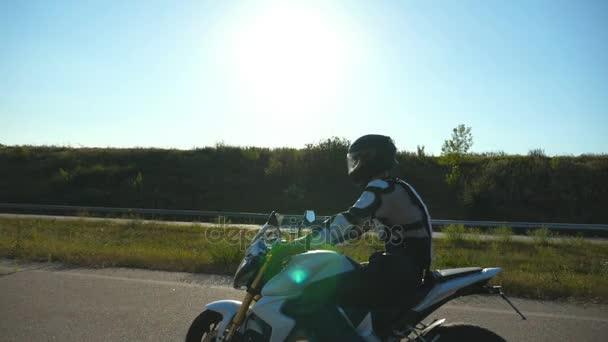 Muž na motorce. Motocyklista jízdy jeho motocyklu na venkovské silnici při západu slunce. Zpomalený pohyb boční pohled zblízka