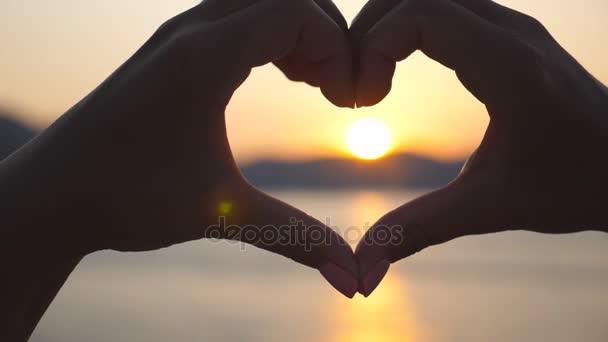 Siluetu mladých fena ruce provedení tvaru srdce přes moře pozadí s krásný západ slunce. Koncept letních prázdnin. Detailní záběr Zpomalený pohyb