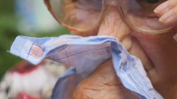 Grandmother in glasses blowing her nose into handkerchief outdoor. Portrait of a sick old woman. Close up Slow motion
