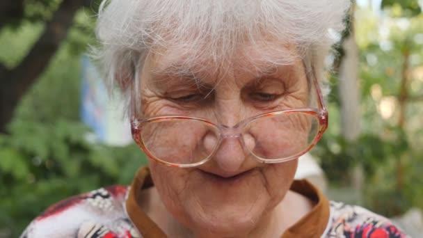 alte Frau mit Brille, die etwas liest und draußen lächelt. Porträt einer glücklichen Oma in Brille, die Zeit draußen verbringt. Gefühle der Großmutter. Zeitlupe in Nahaufnahme