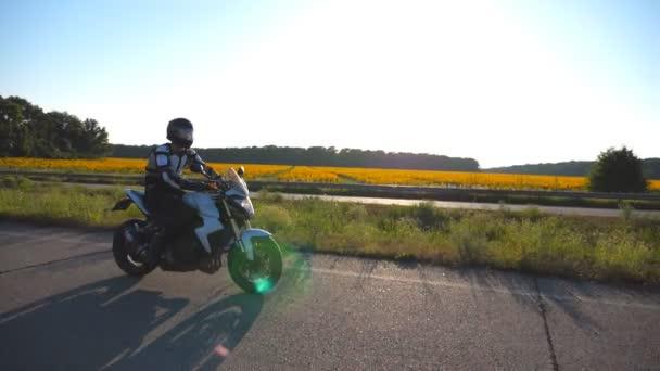 Motocyklista jízdy jeho motocyklu na venkovské silnici s slunečnicová pole v pozadí. Mladý muž v helmě, jízda na kole moto při západu slunce. Zpomalené Detailní záběr