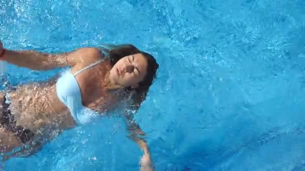 Young beautiful woman swimming on the back at the pool. Girl floating at the basin of hotel and relaxing on sunny day. Summer vacation or holiday concept. Close up Slow motion View from above