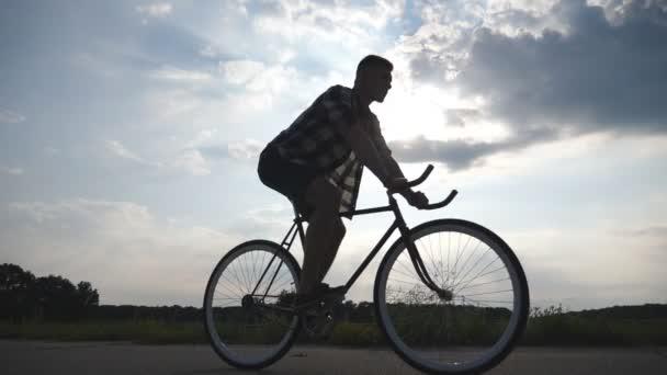 Silueta muže na koni na vintage kolo s krásného západu slunce na obloze v pozadí. Sportovní chlap na kole v zemi silnici. Mužské cyklistu jedoucího pevné ozubené kolo. Zdravý aktivní životní styl zpomalené