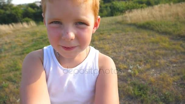 Pěkný dítě hledá se zájmem na fotoaparát, který drží ve svých rukou. Zblízka emoce mužského potomka s vážným výrazem na tváři. Portrét chlapce zrzavé vlasy s pihy. Zpomalený pohyb