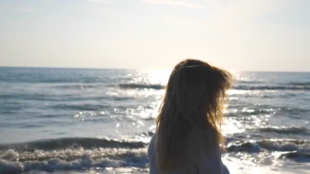 Profile Of Unrecognizable Girl Walking Along Seashore On A Sunny Day Young Woman With Blonde Hair Enjoying Life During Holiday Seaside Landscape At Background Summer Travel Concept Slow Motion