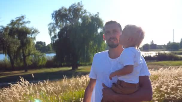 Portrét rodiny na louce za slunečného dne. Mladý otec drží své malé dítě na rukou v oblasti. Otec a syn spolu trávili čas venkovní. Letní krajina na pozadí. Detailní záběr