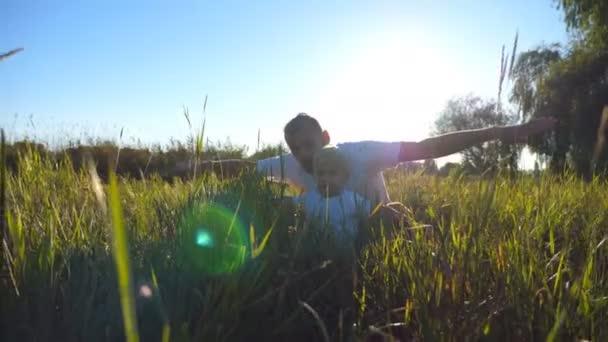Portrét mladého otce a malý syn sedí na zelené trávě a hrát zvedl ruce jako letadlo. Rodina tráví společně čas a užívat si přírody. Sluneční světlo v pozadí. Nízký úhel pohled na plochu