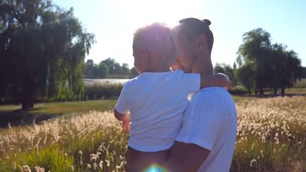 Mladý otec drží své dítě na rukou na louce. Malý syn a pohledný otec ukazující na něco v oboru. Šťastná rodina trávit čas společně. Letní krajina na pozadí. Detailní záběr