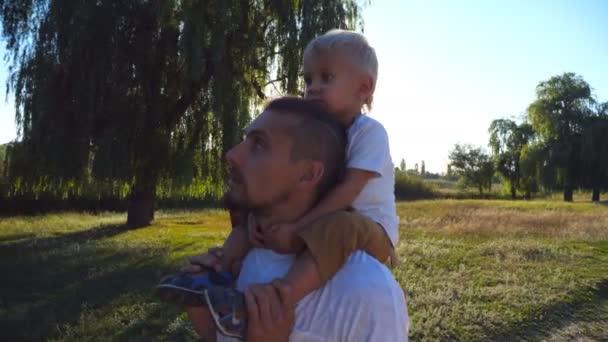 Šťastná rodina chůzi na louce a tatínek ukázal na něco jeho dítě. Chlapeček sedí na ramenou jeho otce a užívání si přírody. Otec a dítě tráví společně čas venkovní. Detailní záběr