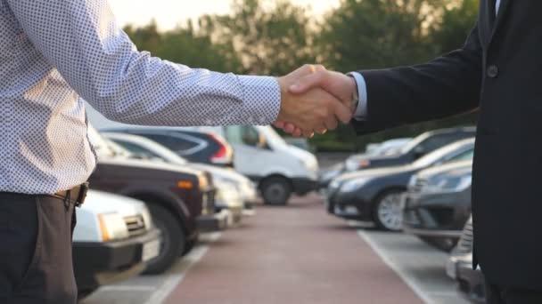 Dva obchodníci si potřásají rukama s auty na parkovišti v pozadí. Potřesení rukou mezi manažerem nebo dealerem a klientem. Potřesení mužských paží venku. Zavřít Zpomalený pohyb