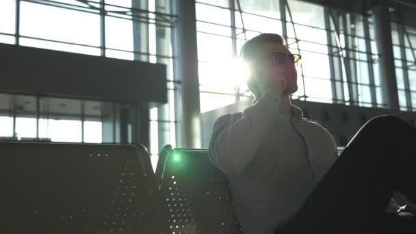 Zavřete portrét pohledný škaredě člověka v sluneční brýle mluvit o mobilní telefon v kanceláři. Mladý podnikatel mluví o telefonu na letišti s odlesk slunce na pozadí. Zpomalený pohyb
