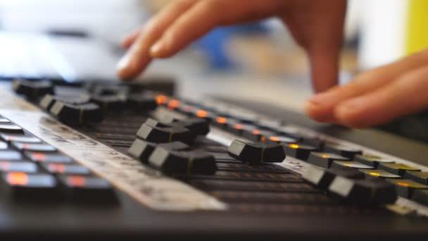 Ruce mužské zvukař stiskne klávesy a tlačítka rezonanční desky se pohybuje. Ruce muže pracující na míchání profesionální digitální audio kanálů. Zesilovač a vyvážení zvuku. Detailní záběr Zpomalený pohyb
