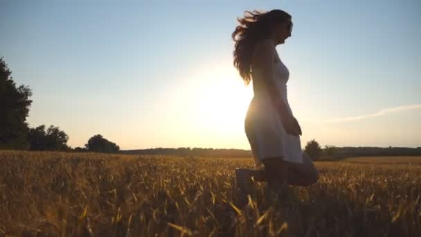 Young girl is running along wheat field under blue sky at sunset. Woman is jogging at the meadow. Sun shine at background. Side view Slow motion