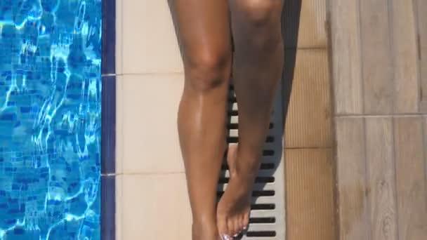 Zár-megjelöl-ból fiatal nő vörösben bikini feküdt a medence szélén, és pihentető a napsütéses napon. Közeli szálloda medencéjét napozóterasz a gyönyörű lány. Nyaralás, vagy üdülési fogalmának. Szemközti nézet