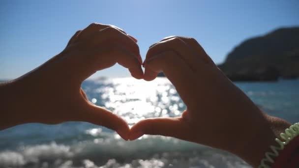 junges Mädchen, das an einem sonnigen Tag mit den Händen vor dem Hintergrund des Meeres Herzformen herstellt. Sommerurlaub am Strand. Ferienkonzept. Nahaufnahme