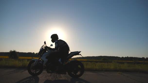 Ember lovaglás egy motorkerékpár, autópálya, háttérben a napkitörések sisak. Motoros vezetés motorjával országúton, naplemente alatt. Lassú mozgás oldalnézetből közelről