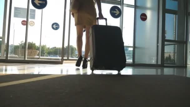 Obchodní lady z letiště se zavazadly. Žena v podpatcích chodit s její kufr přes skleněné dveře od terminálu na parkoviště taxi. Koncept cestování výlet nebo dovolenou. Zpomalený pohyb