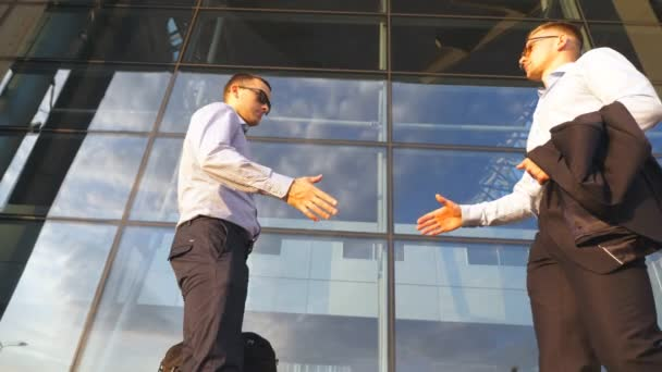 Two businessmen meeting near office and greeting each other. Colleagues shake hands in the urban environment. Business handshake outdoor. Shaking of male arms outside. Close up Slow motion