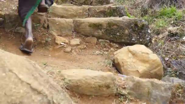 Nízký úhel pohledu indické ženské nohy stoupáme starobylé kamenné schodiště na vrchu. Po k nepoznání žena chodí nahoru schodiště na hoře. Nohy mladá dívka kroků nahoře v ranní