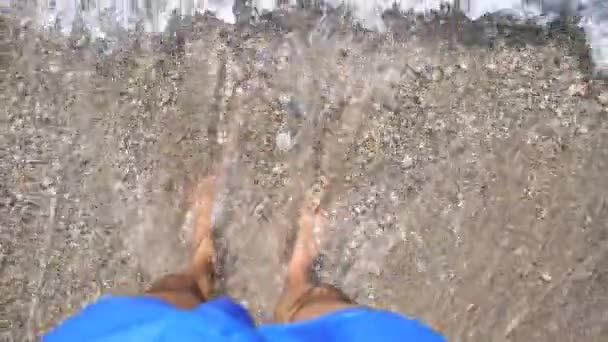 Ocean waves washing over male feet. Young man standing on seashore with pebble and enjoying tides of clear sea water. Guy enjoying summer vacation at seaside. Trip concept. Slow motion Top view POV