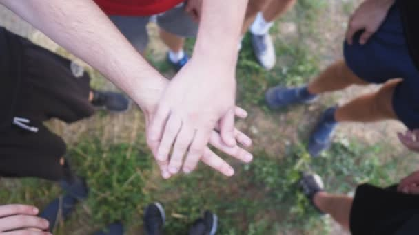 Top view hands of young athletes stacking together one by one in unity. Group of best friends putting their arms in centre of a circle and raising them up. Concept of friendship and teamwork. Slow mo