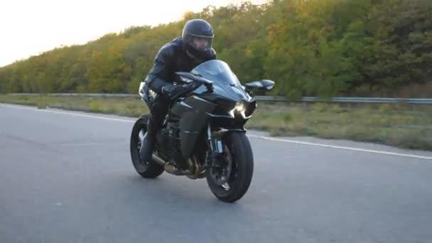 Mladý muž v helmě jezdí rychle na moderní sportovní motorce na dálnici. Motorkář závodní jeho motocykl na venkovské silnici. Chlápek, co jezdí na kole. Pojem svoboda a dobrodružství. Boční pohled