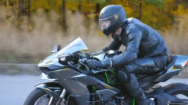 Motorcyclist racing his motorcycle on country road. Guy driving bike during trip. Young man in helmet riding fast on modern sport motorbike at highway. Side view Close up Slow motion